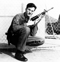Black and white photo of a man in army uniform holding a rifle