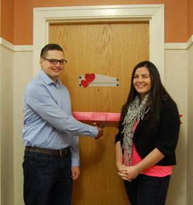 Couple cutting ribbon in front of door