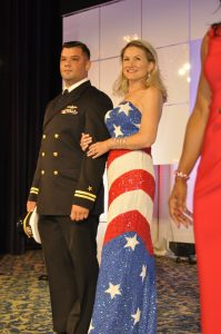 Woman in American flag inspired gown stands next to a man in pilot uniform.