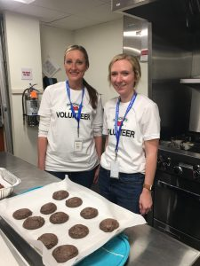 Two volunteers wearing matching shirts baking fresh cookies in the Akron house kitchen