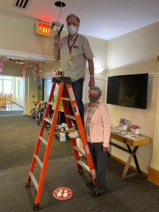 Volunteer supporting another volunteer on a ladder as he replaces a light bulb at Cleveland House