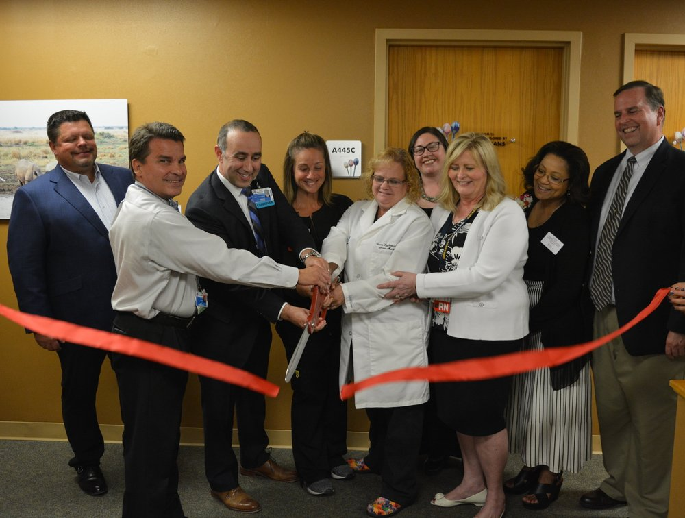 A group of people smiling and cutting a ribbon