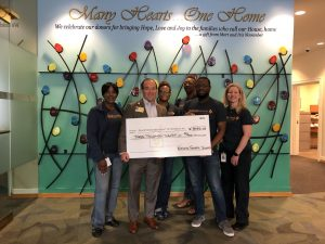 National General Check Presentation group stands in front of a backdrop holding a giant check.