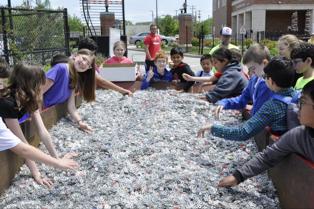 Group of kids around a giant container of donated pull tabs