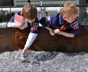 Boy scouts leaning over a bin full of pull tabs